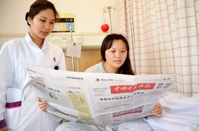 广州中医药大学第三附属医院患者在病房中阅读《中国中医药报》